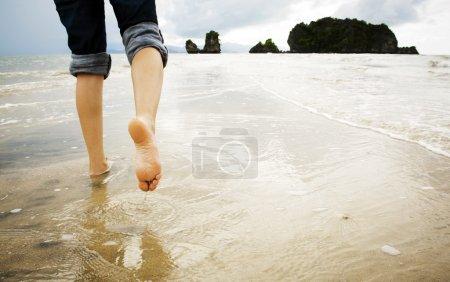 Photo pour Une jeune femme marche seule sur une plage - image libre de droit