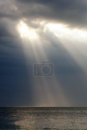 Foto de Asombroso rayo de la luz brilla a través de nubes de tormenta sobre el océano - Imagen libre de derechos