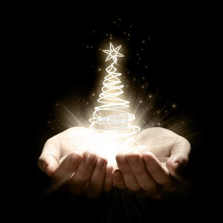 Photo for Two open hands holding a glowing Christmas Tree - Royalty Free Image