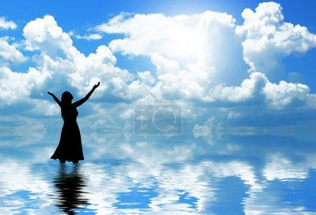 Photo pour Femme levant les mains en louange dans l'eau . - image libre de droit