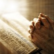 A mans closed hands praying over a Bible...