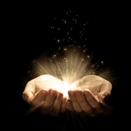 Photo pour Ouvrir les mains avec les paillettes et les lumières rougeoyantes - image libre de droit