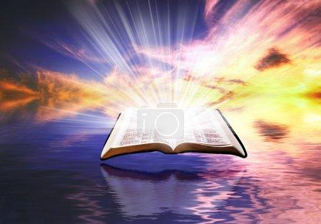 Photo pour Une bible flottante avec des lumières brillantes au coucher du soleil - image libre de droit