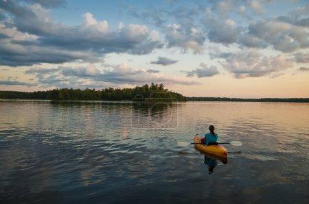 Photo pour Giirl assis dans le kayak sur le lac au coucher du soleil - image libre de droit