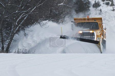 Photo pour Camion chasse-neige sur la route labourant à travers la neige profonde - image libre de droit