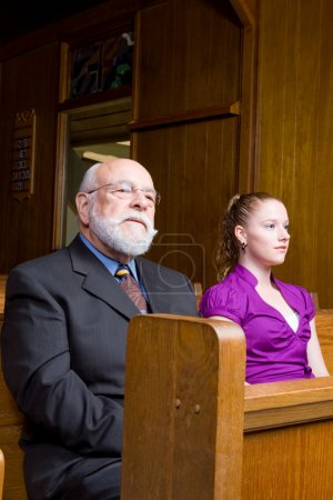Photo for Senior man and young woman sitting in a church pew - Royalty Free Image