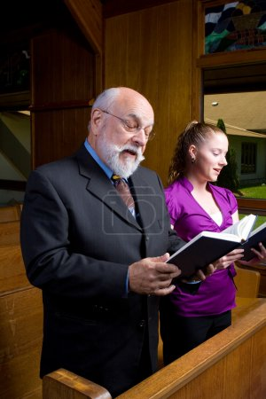 Young Woman Caucasian Man Standing Singing Hymnals