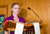 Young Caucasian Woman Reading from Bible at Church Lectern