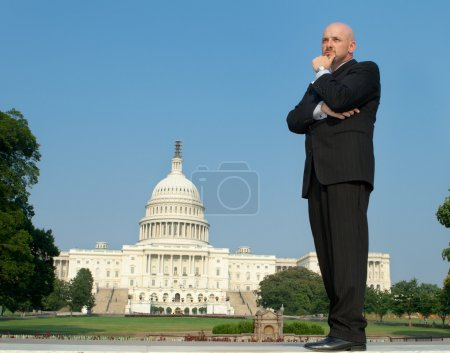 Photo pour Type Power broker dans un costume, la main sur le menton debout devant l'US captiol bâtiment, downtown washington, dc, é.-u.. - image libre de droit