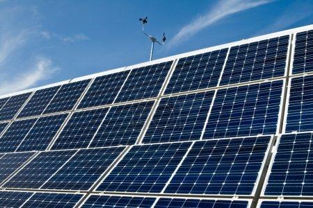 Foto de Matriz de panel solar PV con un anemómetro con un cielo azul de fondo. - Imagen libre de derechos