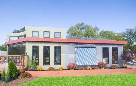 Foto de Moderna casa solar con un calentador de agua solar en el frente y los paneles solares fotovoltaicos en el techo. - Imagen libre de derechos