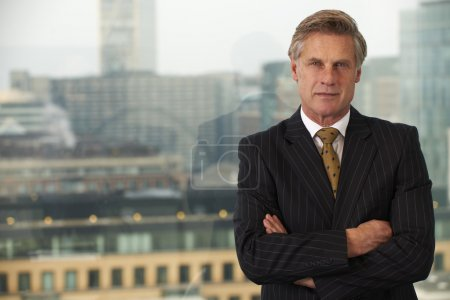 Photo for Portrait of a senior executive by a window smiling looking at camera with space for copy - Royalty Free Image