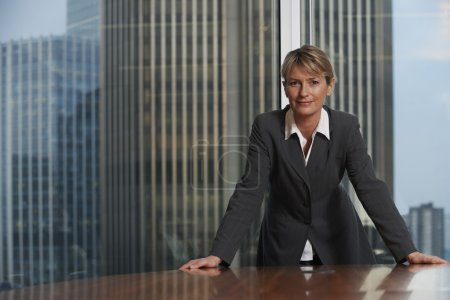 Photo for Business woman leaning on chair in boardroom looking at camera - Royalty Free Image