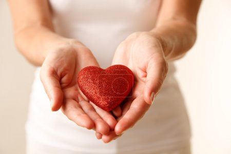Photo for Giving love concept with hands holding a red heart. - Royalty Free Image