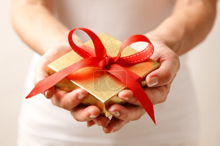 Photo for Woman holding a gift box in a gesture of giving. - Royalty Free Image