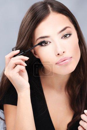 Pretty woman applying mascara on her lashes