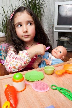 Photo pour Petite fille jouant à l'intérieur, nourrissant sa poupée - image libre de droit