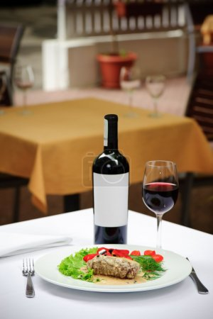 Filletto al pepe verde and wine served at white tablecloth