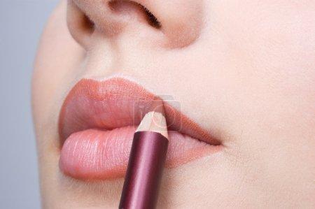 Photo pour Maquillage, appliquer le crayon liner lèvres sur belles lèvres - image libre de droit