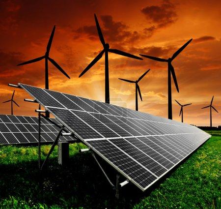 Foto de Paneles de energía solar y de la turbina de viento en la puesta de sol - Imagen libre de derechos