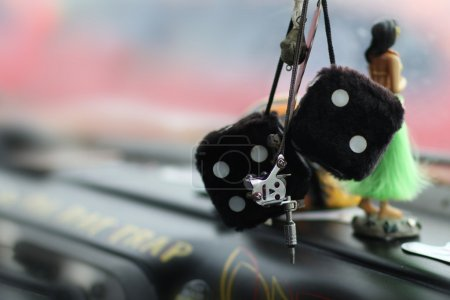 Photo for Two black dice hang from a rear view mirror in a vintage car, while a Hawaiian doll with a green grass skirt rests on the dashboard in the background. - Royalty Free Image