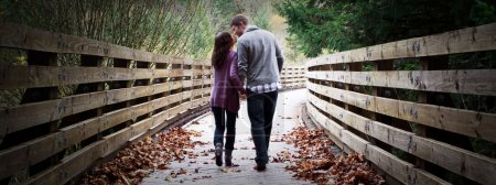 Photo pour Jeune couple fiancé marchant le long d'un sentier en bois . - image libre de droit