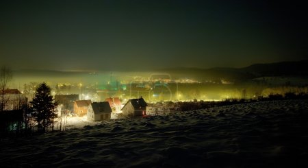 Night winter view on the small town with mist
