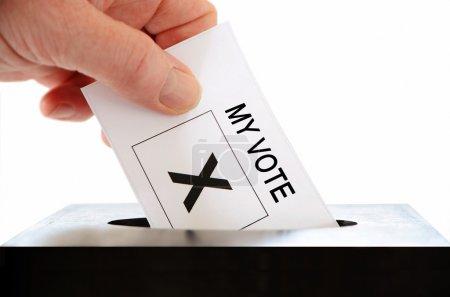 Photo pour Une main en plaçant un feuillet avec droit de vote dans une urne sur un fond blanc - image libre de droit